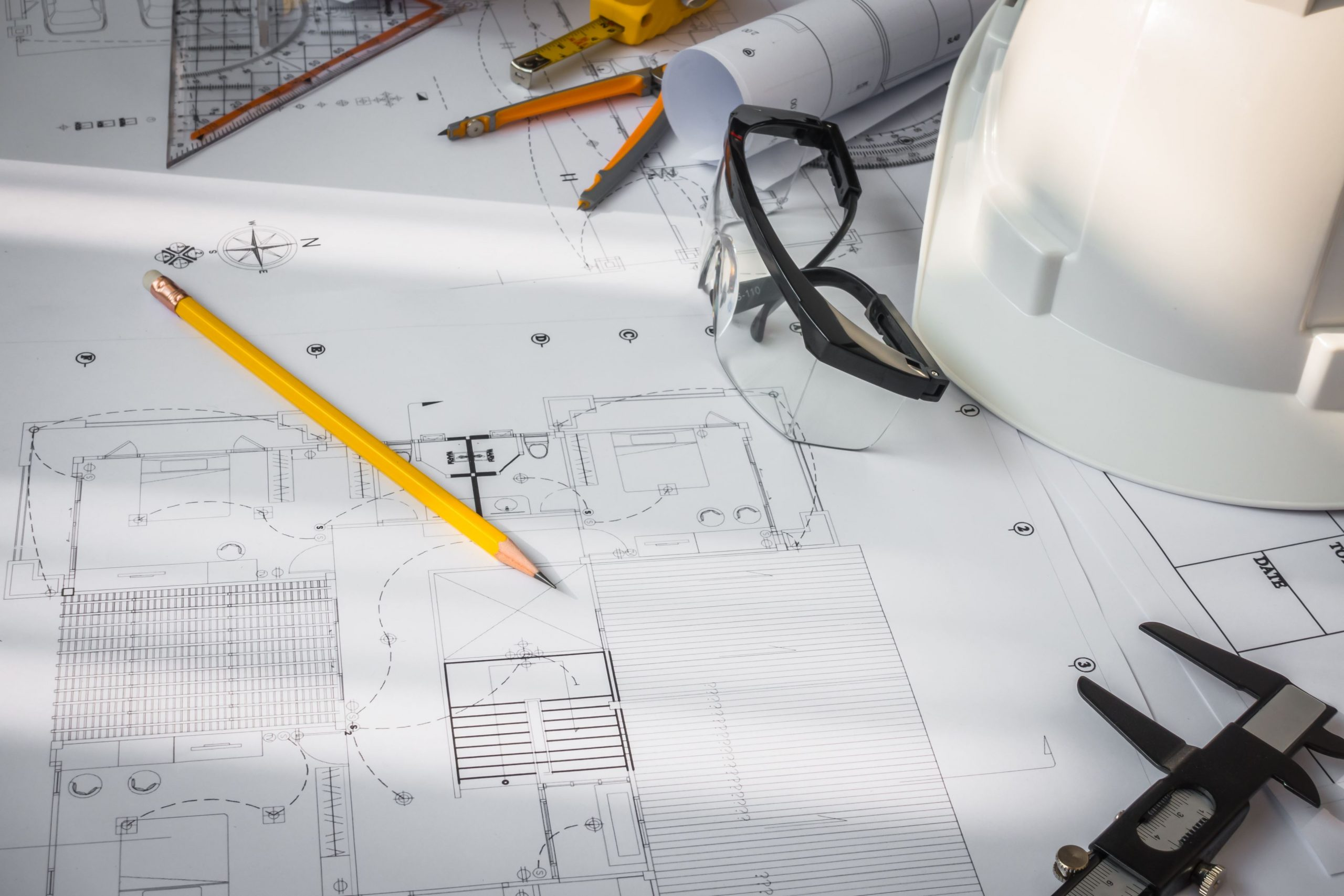 Construction plans with White helmet and drawing tools on blueprints - printmydrawings